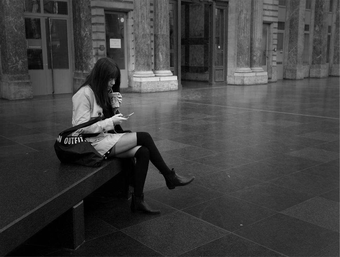 Straatfoto van vrouw met gsm